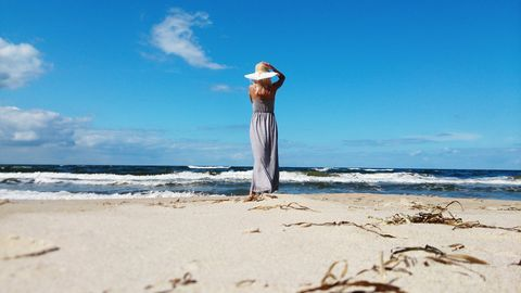 Rear view of a woman standing on beach