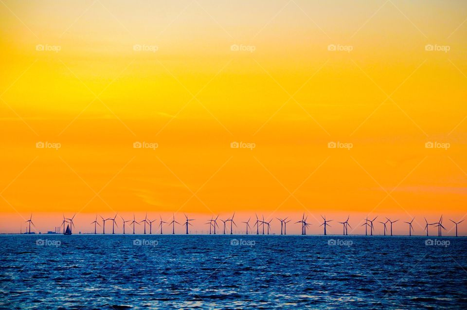 View of sea with wind turbine against dramatic sky