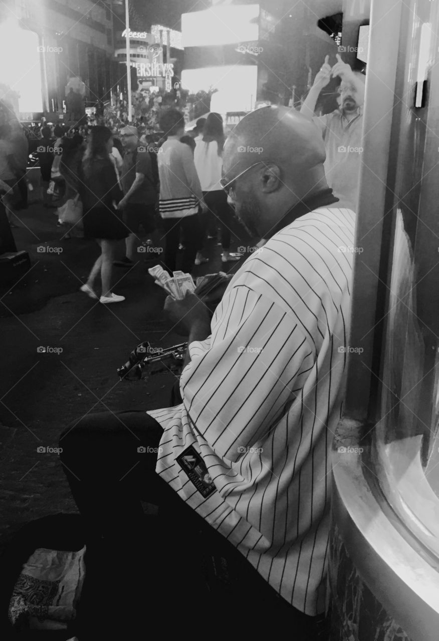 Musician counting the money in a street of New York near Times Square