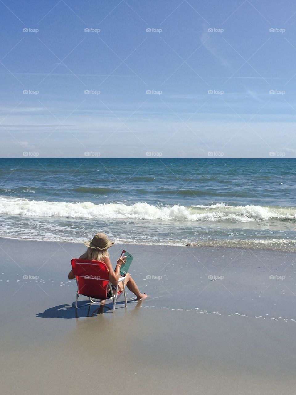 A woman enjoys a good book sitting along the seashore in Myrtle Beach South Carolina.