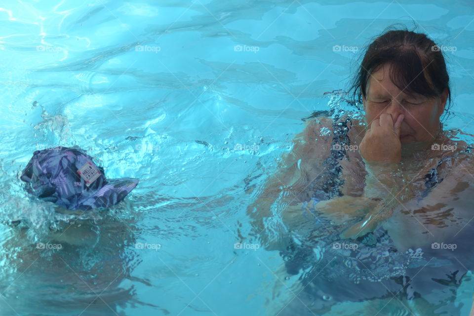 Woman in the swimming pool closing her nose