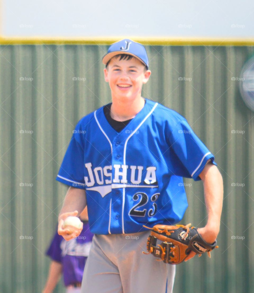 Teenager baseball pitcher holding ball with glove