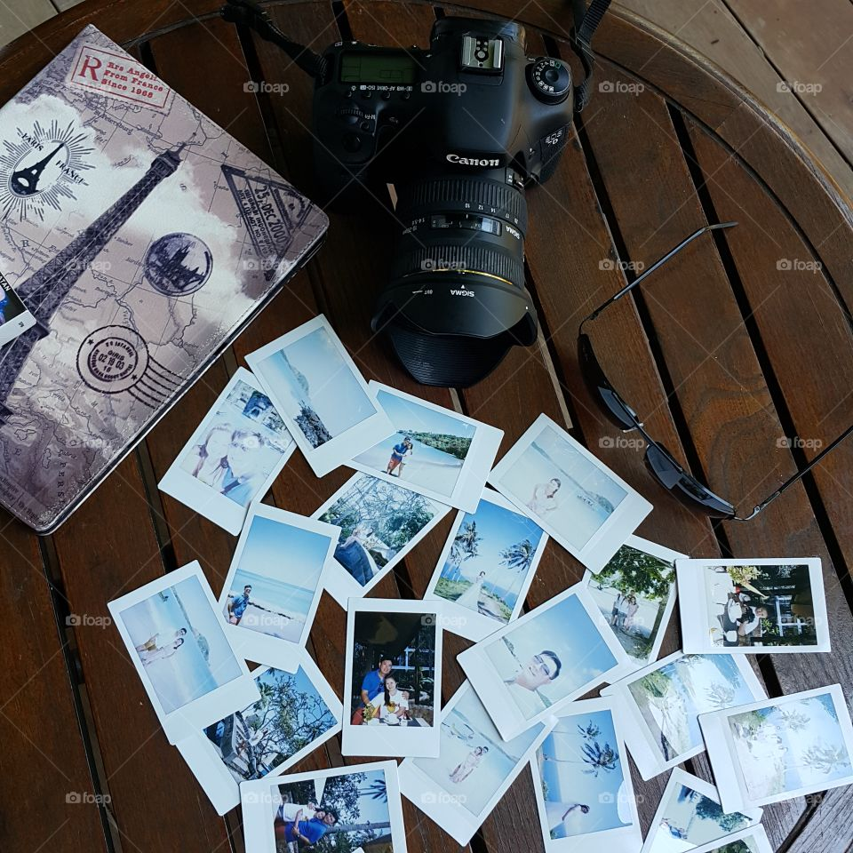 High angle view of photographs with camera on wooden table
