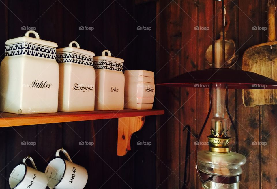 Ceramic containers on shelf with lamp and measuring cup