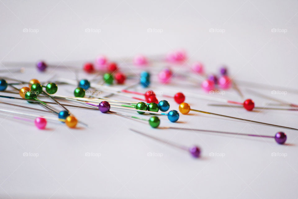 Multi colored push pin on white background