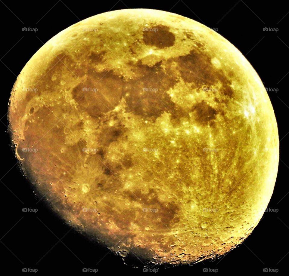 Fast Vollmond, leuchtend gelb kurz vor der rötlichen Blutmond Färbung am nachtschwarzen Himmel