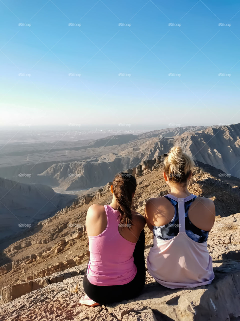Friends sitting on the top of the mountain watching beautiful landscape