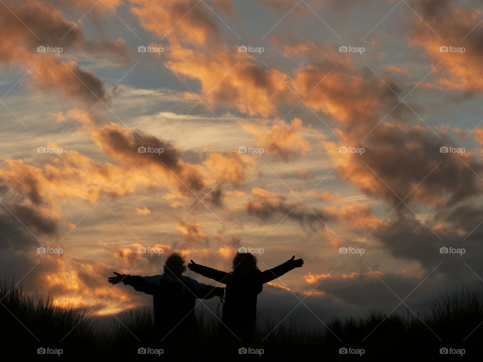 Silhouette of Best Friends On A Hill Embracing A Beautiful Sunset Sky With Hands In The Air - Celebration