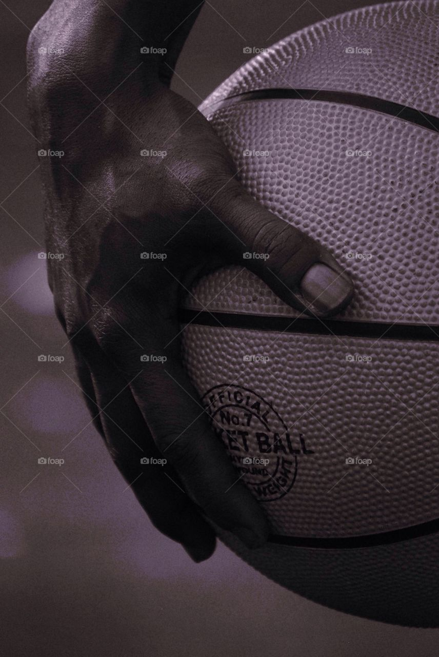 Close-up of players hand holding basket ball