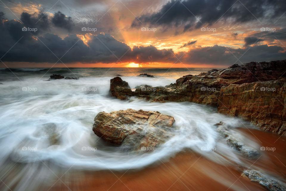 Dramatic sunrise with motion waves at Kemasik Beach, Terengganu