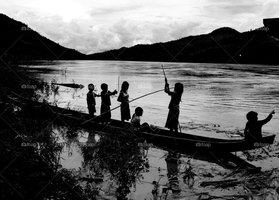 children silhouette driving a boat