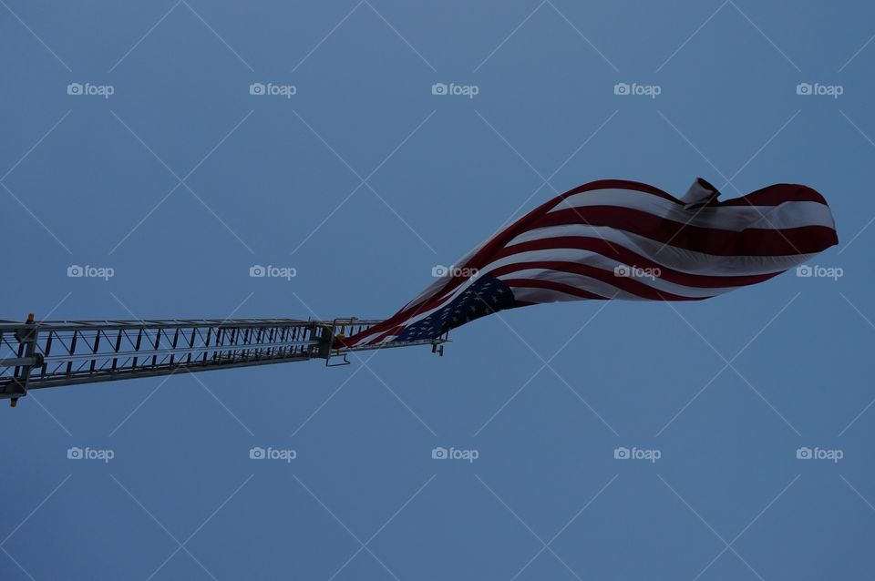 Fire truck ladder flying flag. Looking straight up at the U.S. Flag flying from the fire trucks extended ladder.