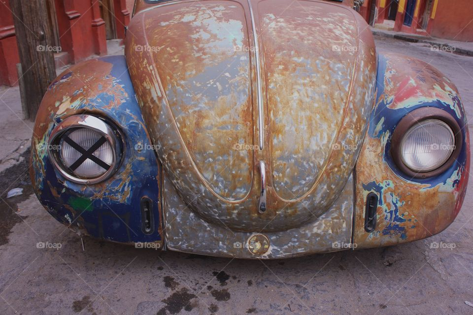 A front abstract view of an old Volkswagen  Beetle's headlights and fenders on a street in San Miguel de Allende, Mexico.