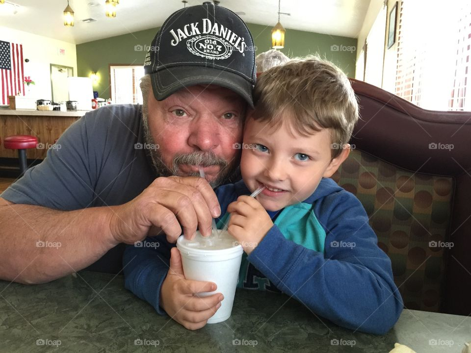Cute little son and his father drinking milkshake