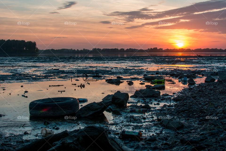 View of garbage in lake at sunset