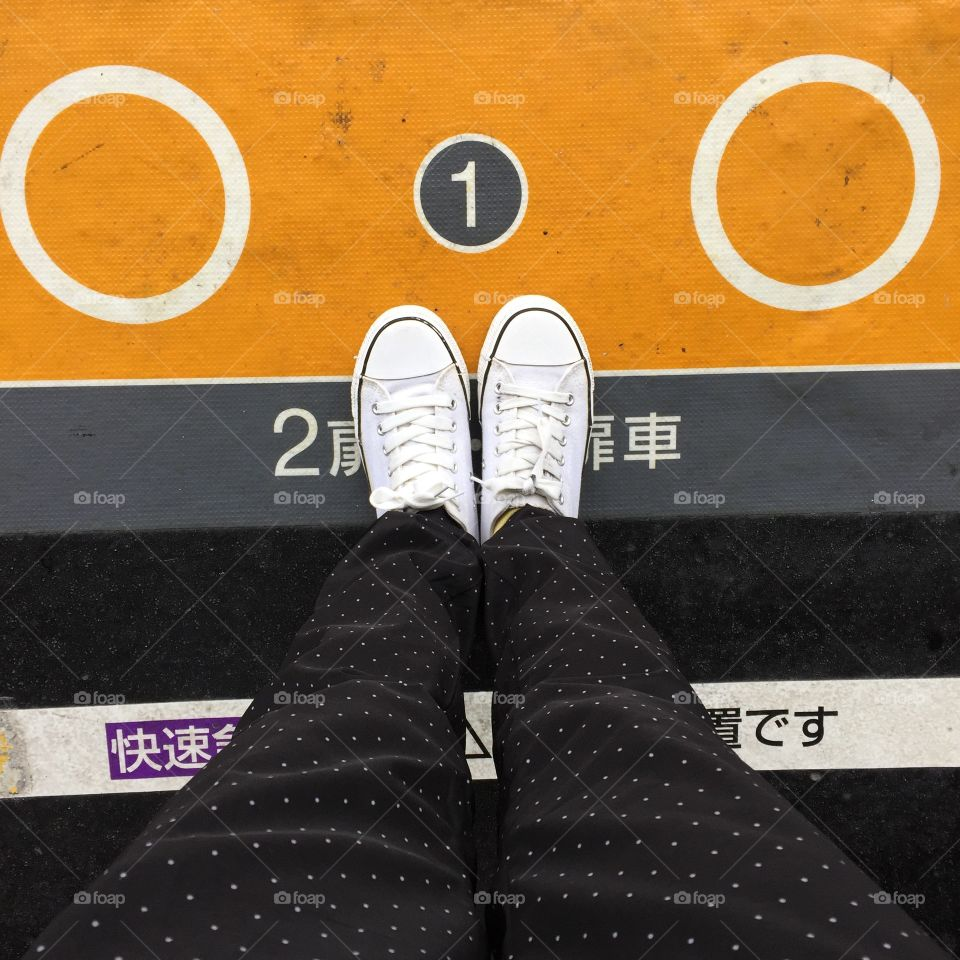 Close-up Picture of Woman Who Crossed Her Legs. Woman in Black Jeans and Sneakers Enjoying Daytime