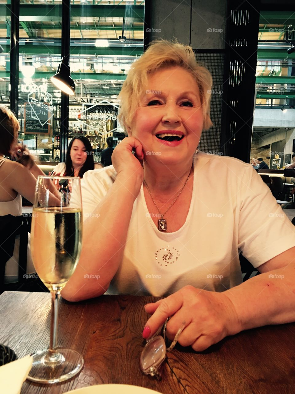 Smiling mature woman sitting with wine glass in restaurant