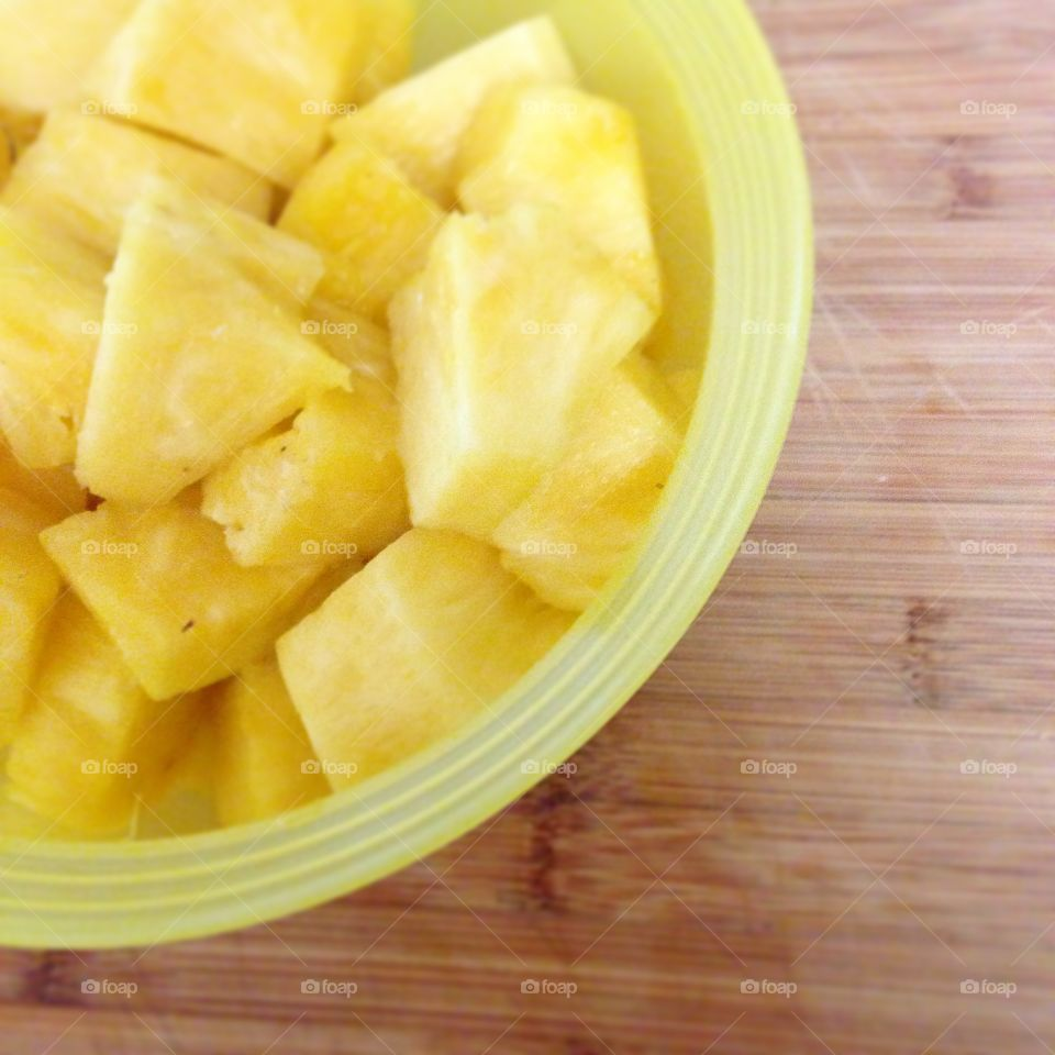 Sunny Pineapple. Freshly cut pineapple in a yellow bowl on a wooden cutting board.
