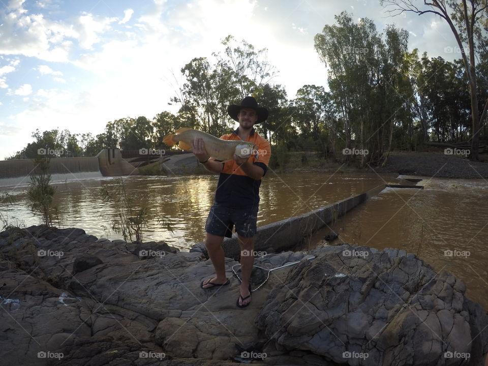 Man showing fish near river