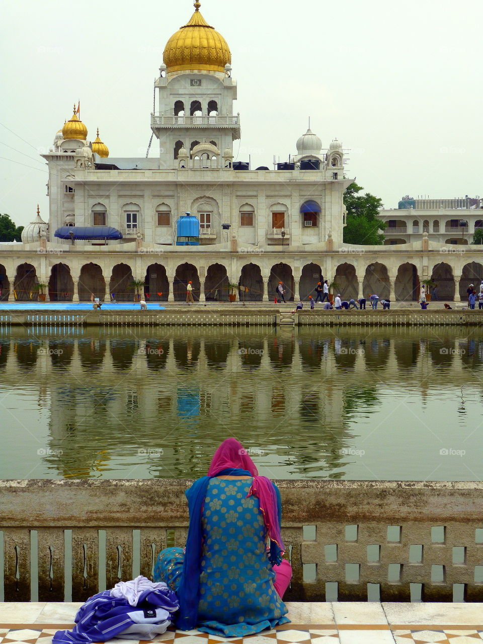 sitting near the water in front of the indian temple