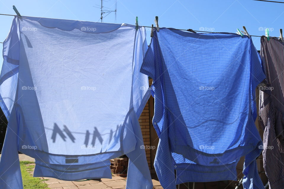 Clothesline and clothespin clothes pegs shadows through hanging laundry on outdoor laundry line on sunny day