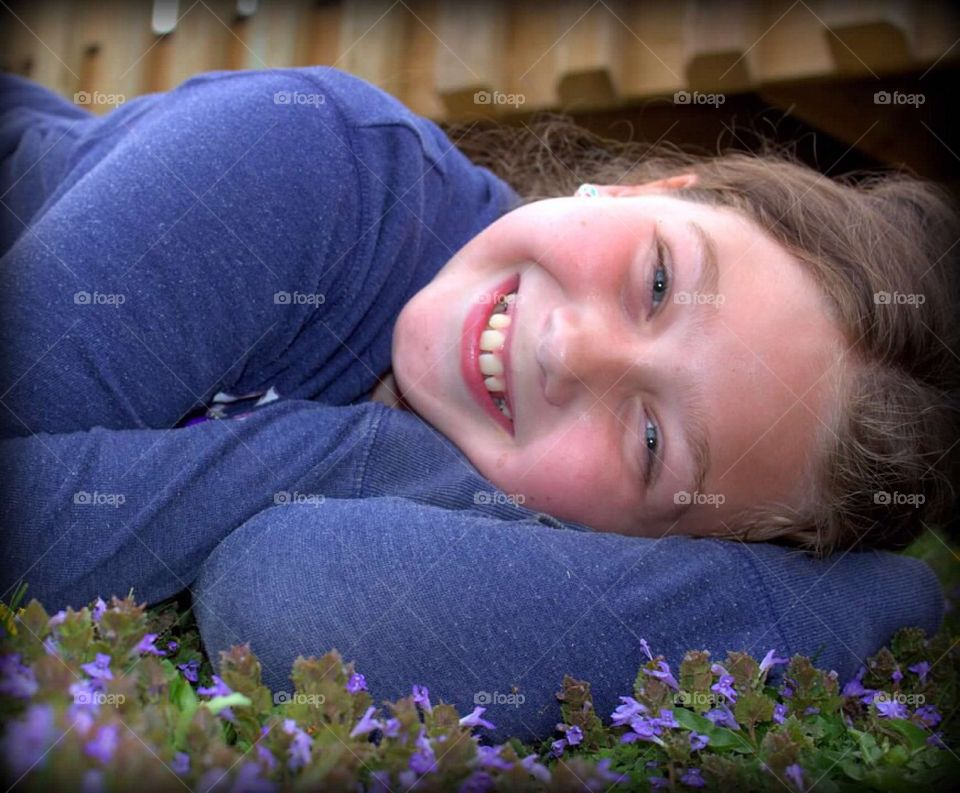 My beautiful nine-year-old daughter laying in a patch of pretty, purple flowers.
