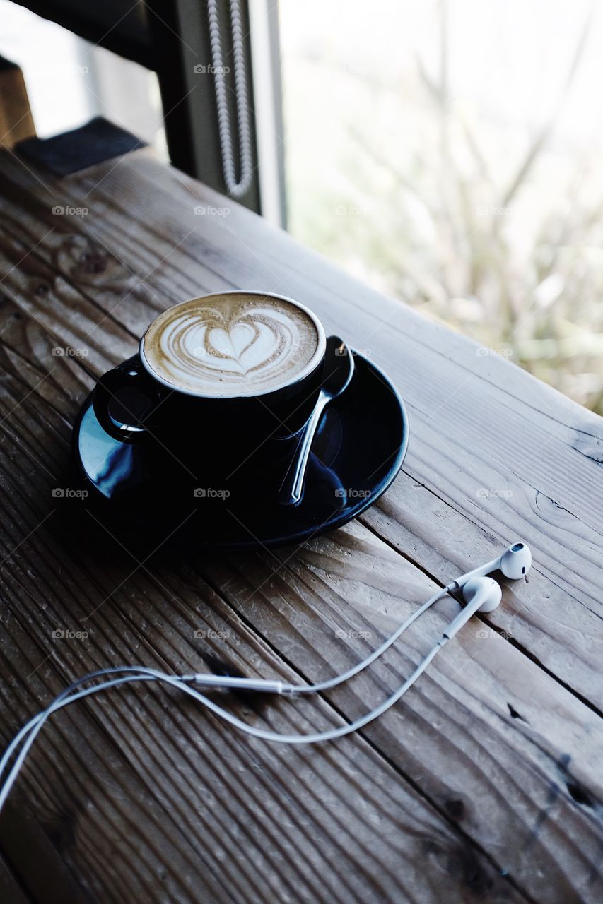 Cappuccino sitting in a window next to a pair of Apple earbud headphones.