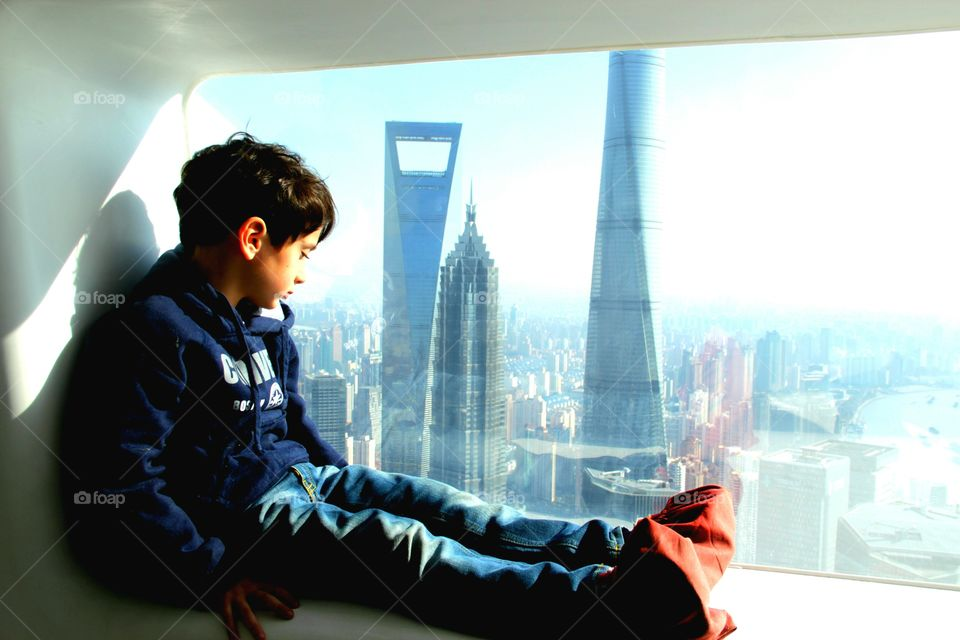 A cute 4 years old Little boy contemplates the view of PuDong skyscrapes, sitting at the windows of the Space Module from the Pearl Tower in Shanghai, 370 meter High, 2015
