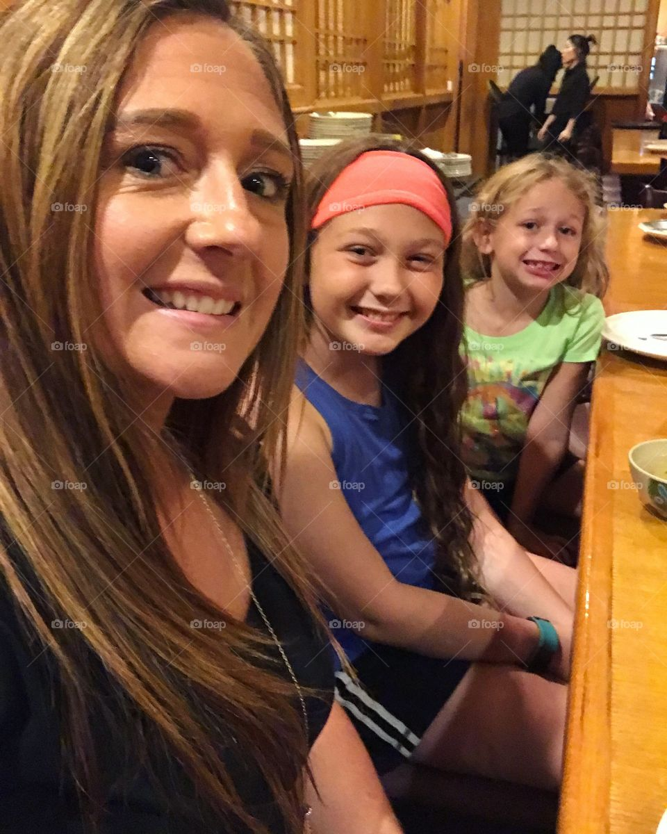 Close-up of a mother sitting in restaurant with her daughters