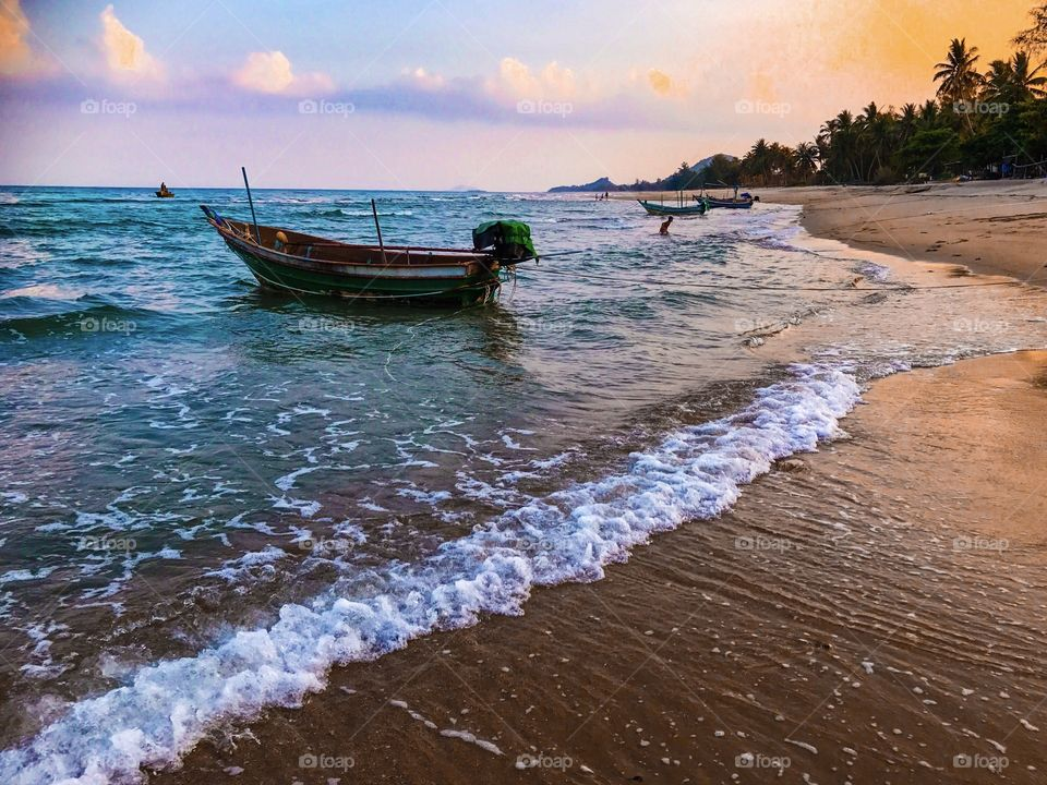 Romantic holiday vacation on tropical sandy beach seaside with fishing boats seen during sunset in southern Thailand - colorful ocean theme background