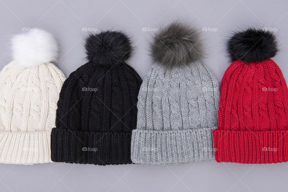 Flat lay of a row of different colored pom pom beanie hats