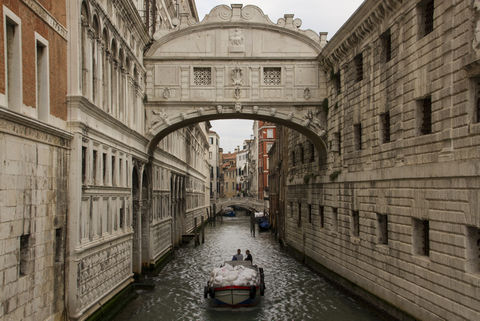 Waste collection boat rides underneath Bridge of sighs, Venice.