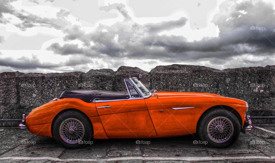A red classic car on a stone harbour colour pop.