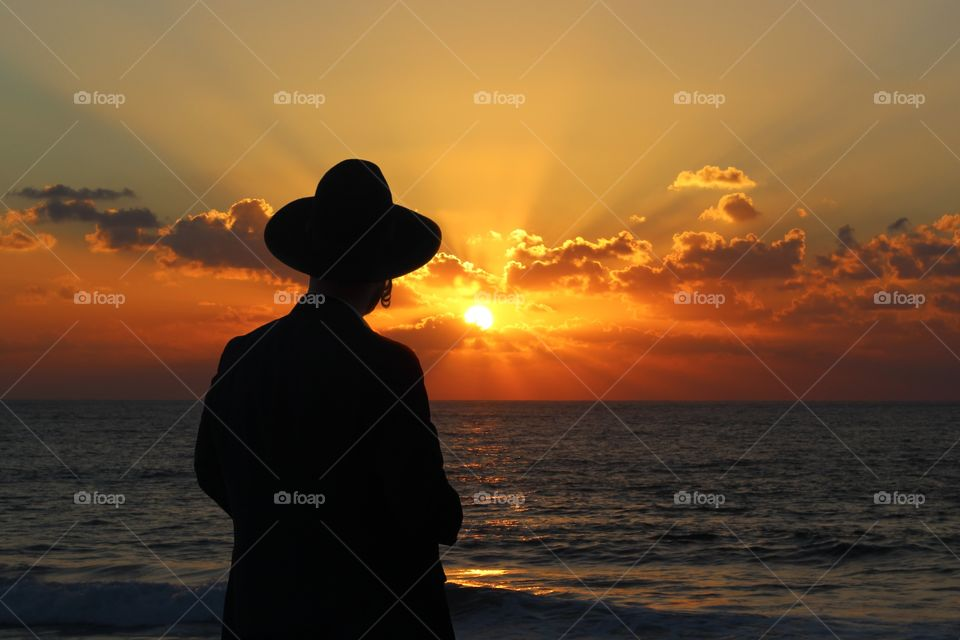 A religious Jew standing on the coast of Mediterranean sea and watching the sunset, deep in thought.
