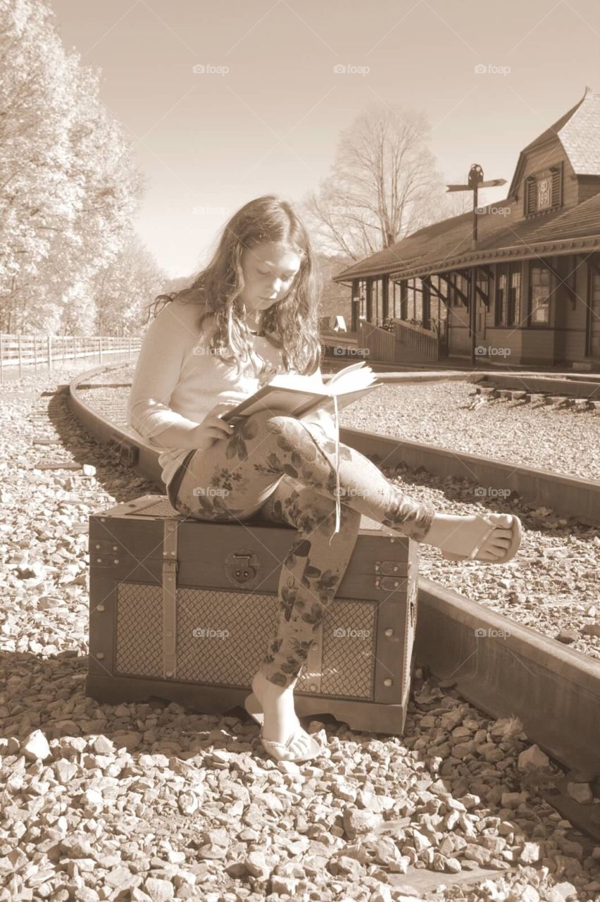 Young lady, reading a book, waiting on a train.