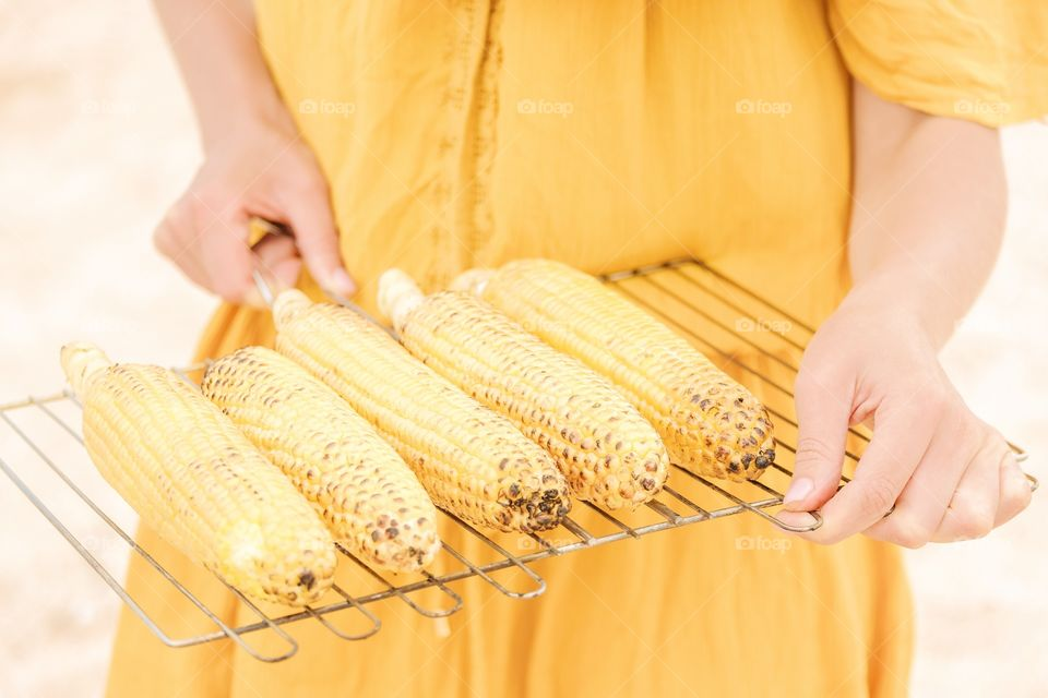 The girl in a yellow dress is holding grilled corn