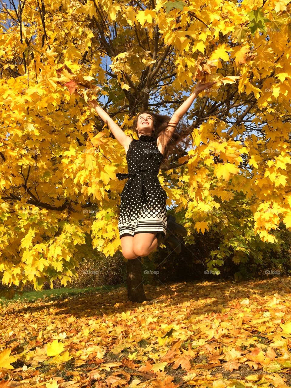 Yellow happiness . Jumping in the autumn yellow leaves