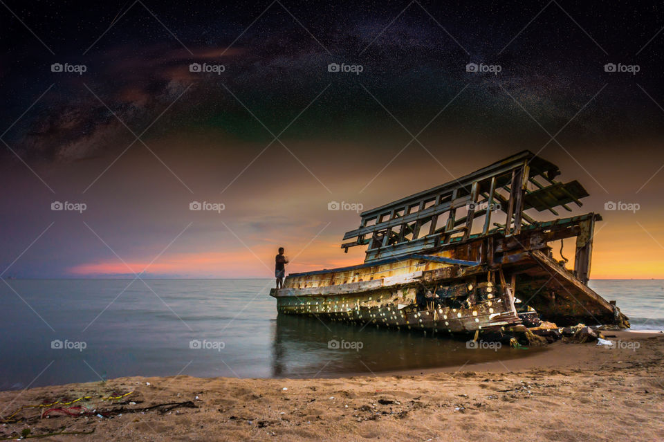 wreck on the beach and milky way