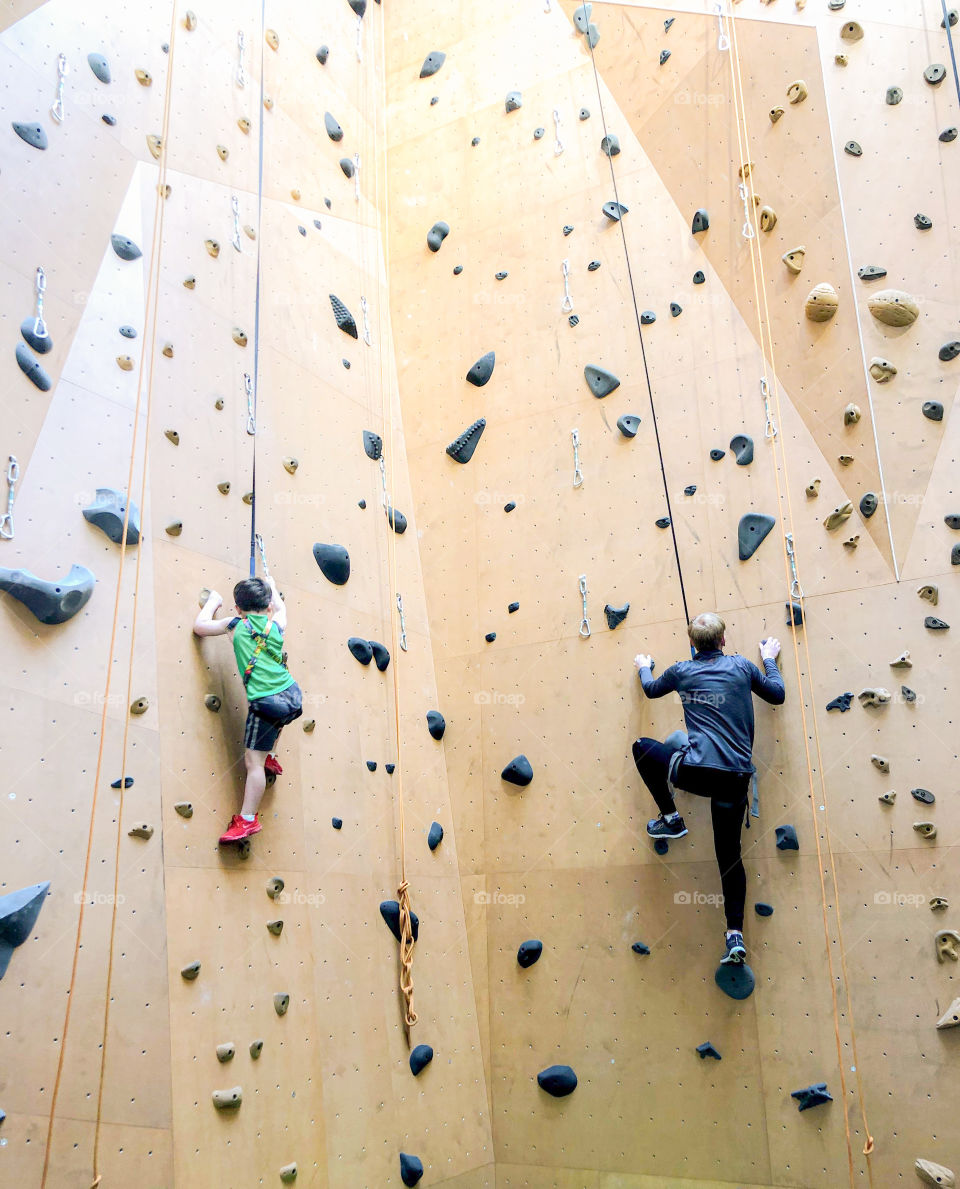 Father and son race to the top of the climbing wall at The St. James gym.