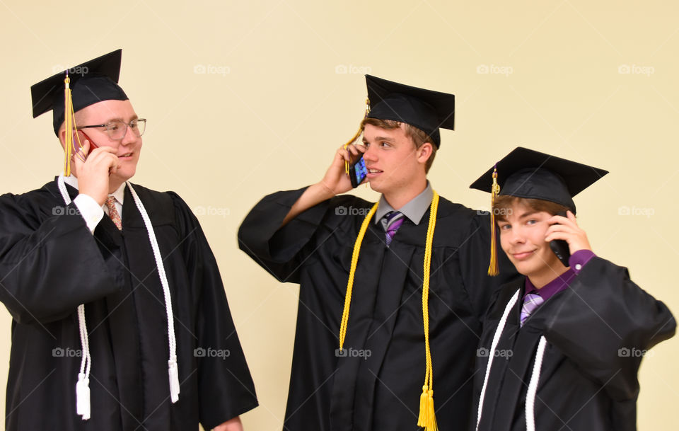 Graduates using their cell phone