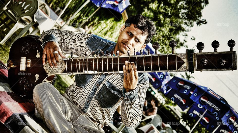 Indian man concentrates as he plays the Sitar, Agra, India . Indian man concentrates as he plays the Sitar, Agra, India