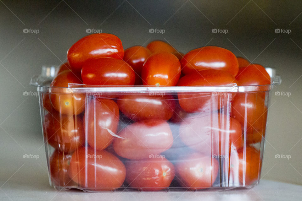 Red mini tomatoes in a plastic box