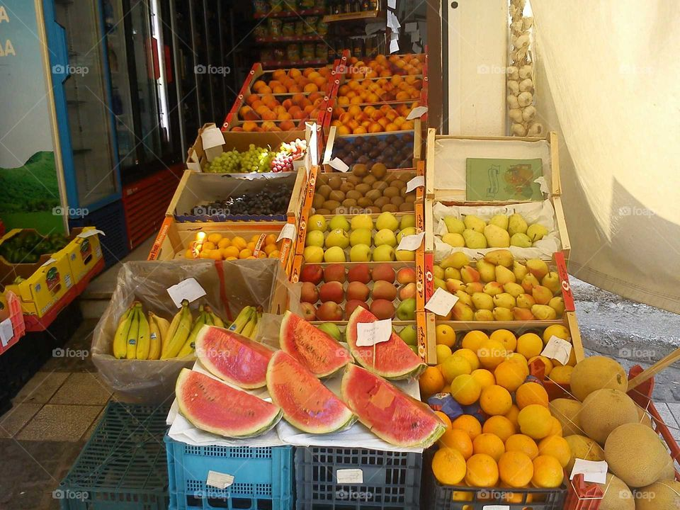 fruit rainbow in beautiful Parga, Greece. all sorts of food in a traditional market store in Greece. oranges, pears, appricots, melons, watermelons, bananas, peaches, grapes, coconuts.