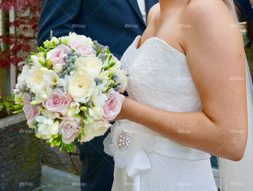Mid section of bride and groom with flower bouquet