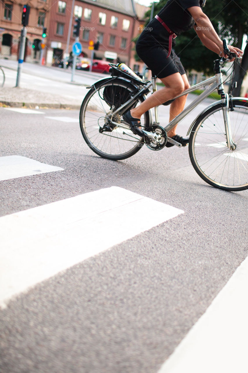 Woman riding bicycle over pedestrian crossing