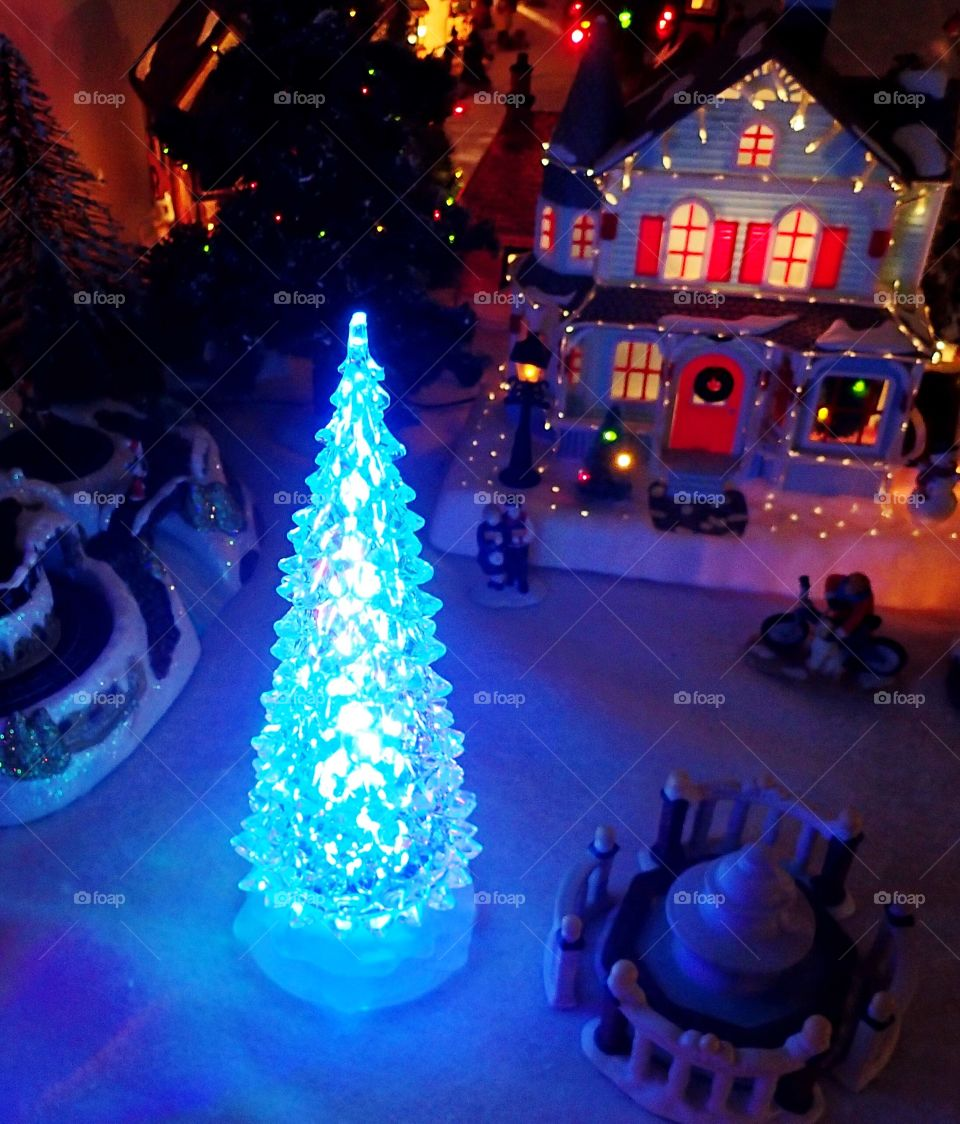 A bright blue tree in a Christmas village display.