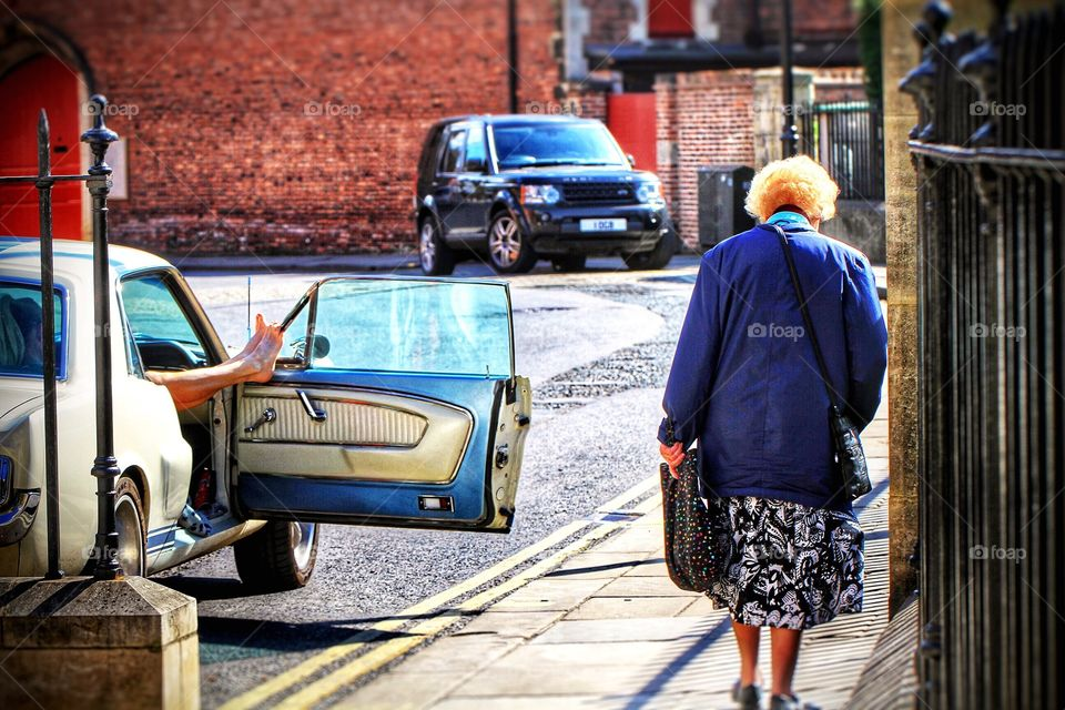An old lady walks past a parked, classic American car with a young girl resting her feet on the open door in the city of York.