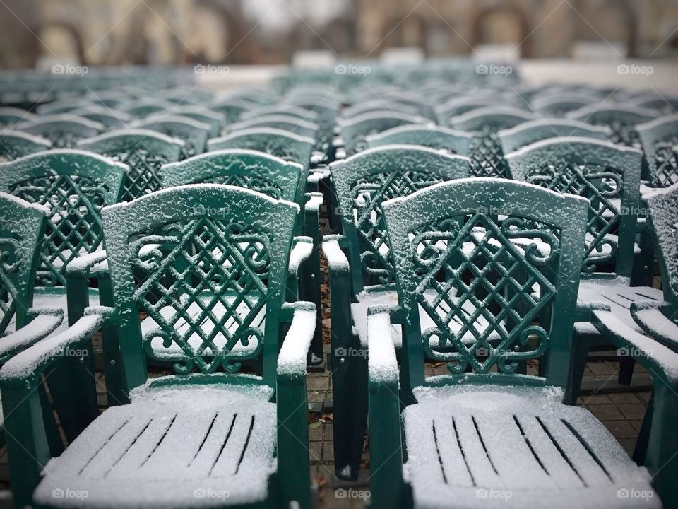 Snow on green chairs