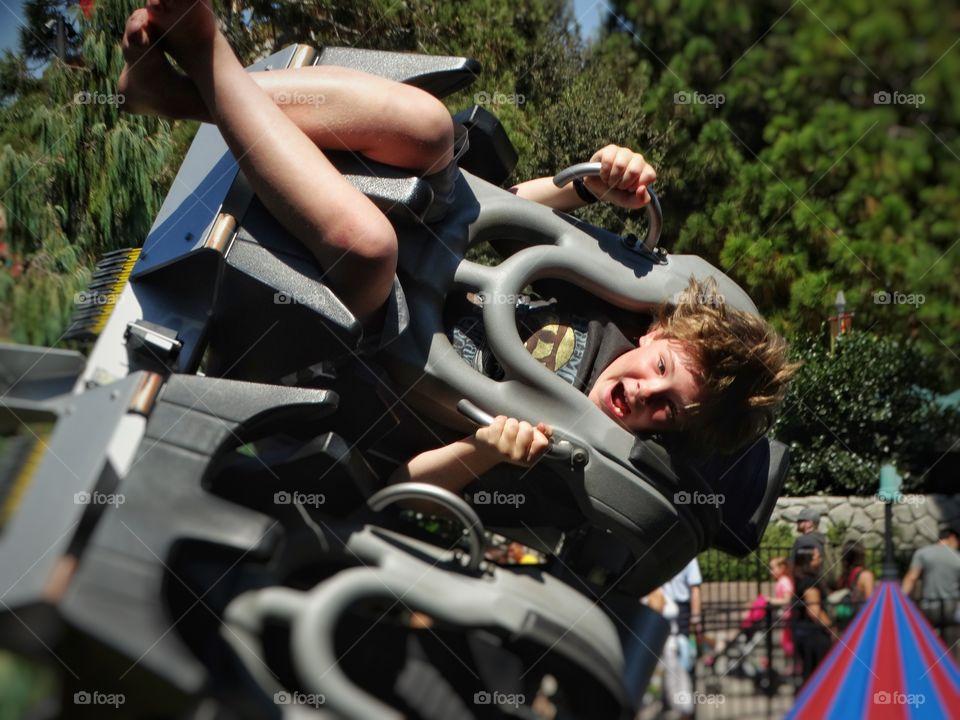 Boy enjoying ride at amusement park