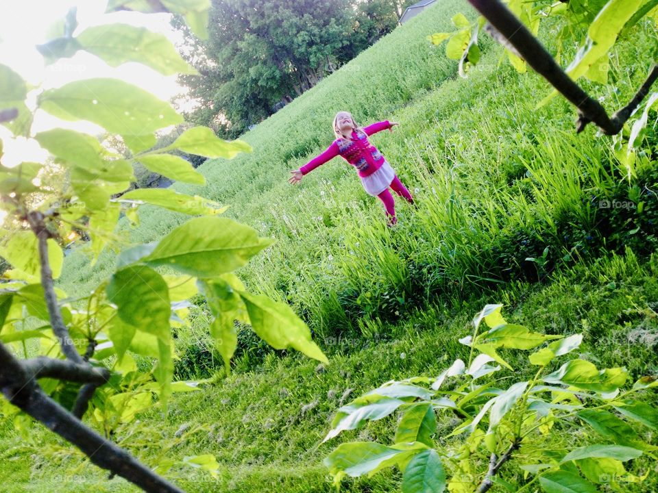 Gorgeous cloudy afternoon and little girl in bright pink colors is thoroughly enjoying it surrounded by a beautiful green grassy field and trees!
